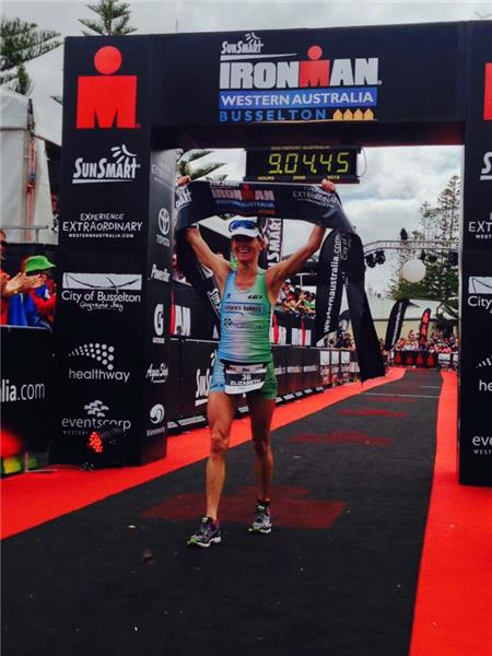 An elated Elizabeth Lyles raising the banner over the line. Photo: IronmanLive / Delly Carr