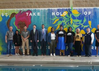 Representatives from the IRONMAN Foundation, The IRONMAN Group, Tulsa Mayor G.T. Bynum, Black Moon Collective, local Tulsa YMCA and Boys & Girls Club, Professional triathlete Matt Russell pose in front of a new mural that was commissioned at the W.L. Hutcherson YMCA. (Photo Credit: BCC Live for IRONMAN Foundation)
